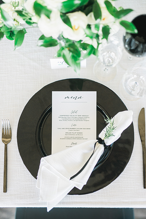 black plates on a white table linen with gold flatware