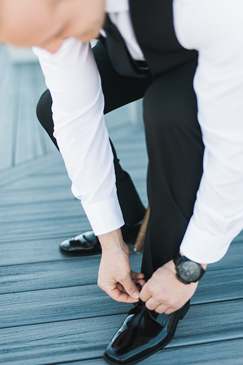 groom in a black tuxedo tying his shoes