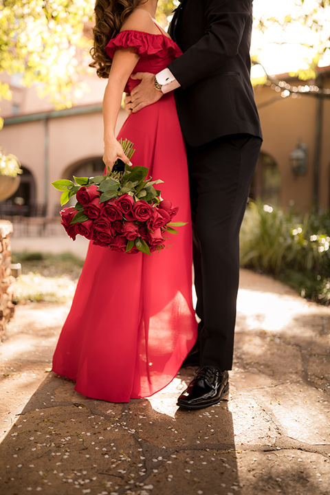 girl in a long red dress with an off the shoulder detail and roses and man in a black tuxedo with a shawl lapel tuxedo and a black bow tie