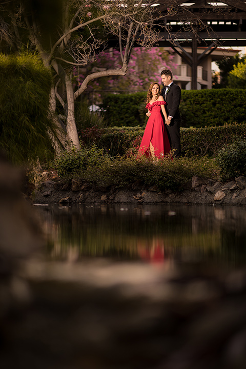 girl in a long red dress with an off the shoulder detail and roses and man in a black tuxedo with a shawl lapel tuxedo and a black bow tie dancing in the park