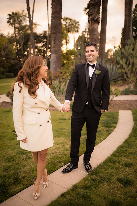 girl in a long cream trench coat and man in a black tuxedo with a shawl lapel tuxedo and a black bow tie dancing in the park