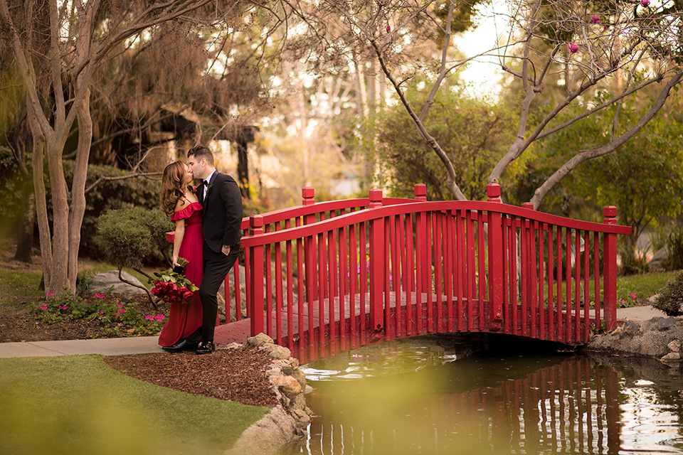 girl in a long red dress with an off the shoulder detail and roses and man in a black tuxedo with a shawl lapel tuxedo and a black bow tie by the bridge