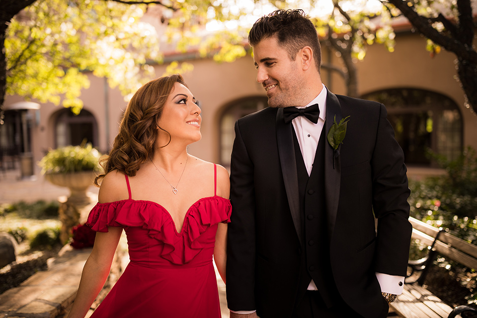 girl in a long red dress with an off the shoulder detail and roses and man in a black tuxedo with a shawl lapel tuxedo and a black bow tie walking in the park