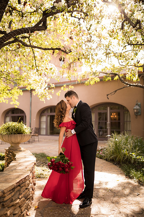 girl in a long red dress with an off the shoulder detail and roses and man in a black tuxedo with a shawl lapel tuxedo and a black bow tie kissing in the park