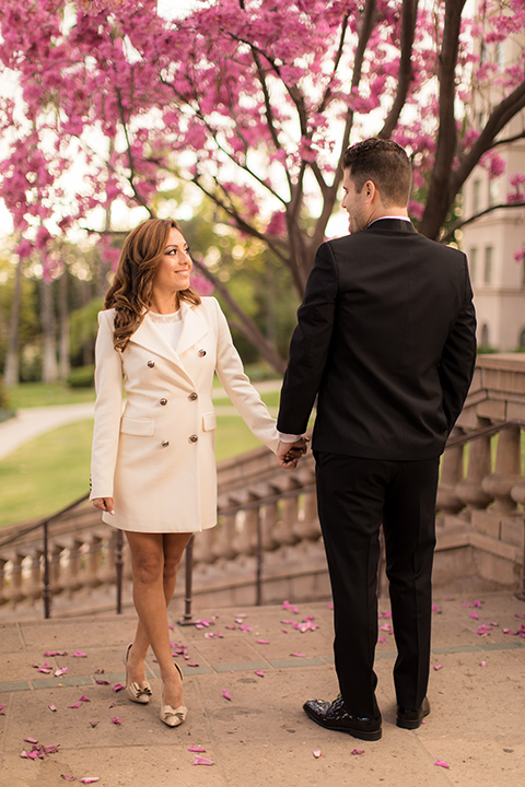 girl in a long white trench coat and man in a black tuxedo with a shawl lapel tuxedo and a black bow tie twirling