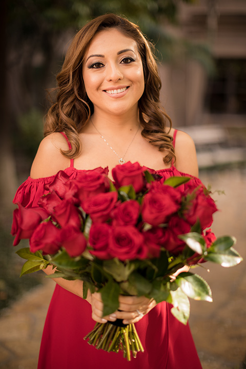 girl in a long red dress with an off the shoulder detail and roses