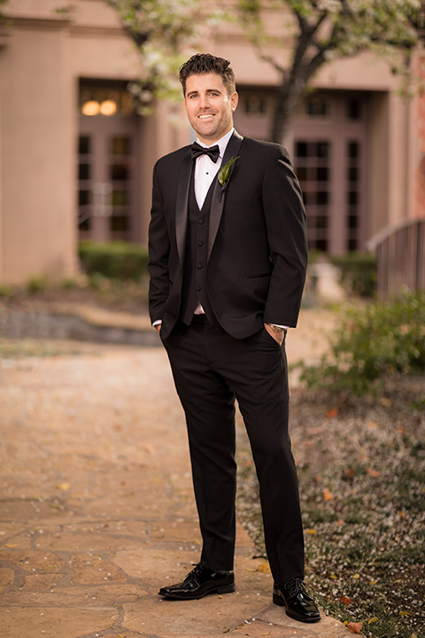 man in a black tuxedo with a shawl lapel tuxedo and a black bow tie