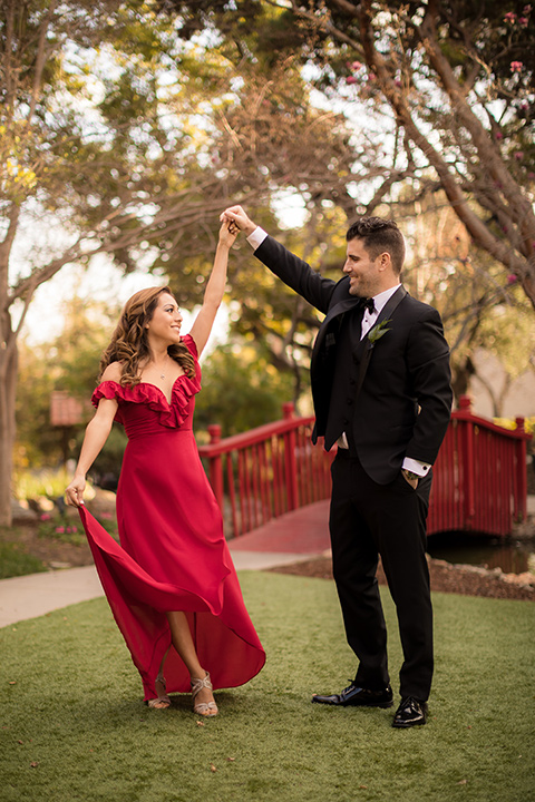 girl in a long red dress with an off the shoulder detail and roses and man in a black tuxedo with a shawl lapel tuxedo and a black bow tie twirling