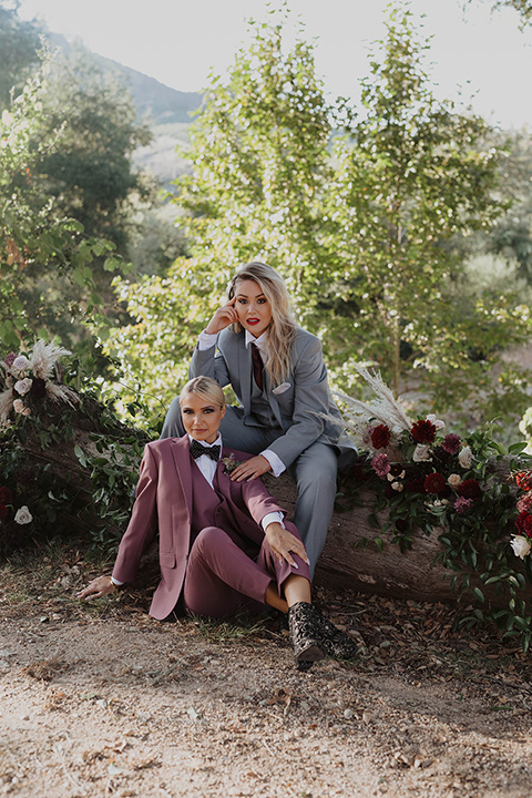one bride wearing a rose pink suit with a geometric bow tie and the other wearing a light blue suit and a wine burgundy colored bow tie