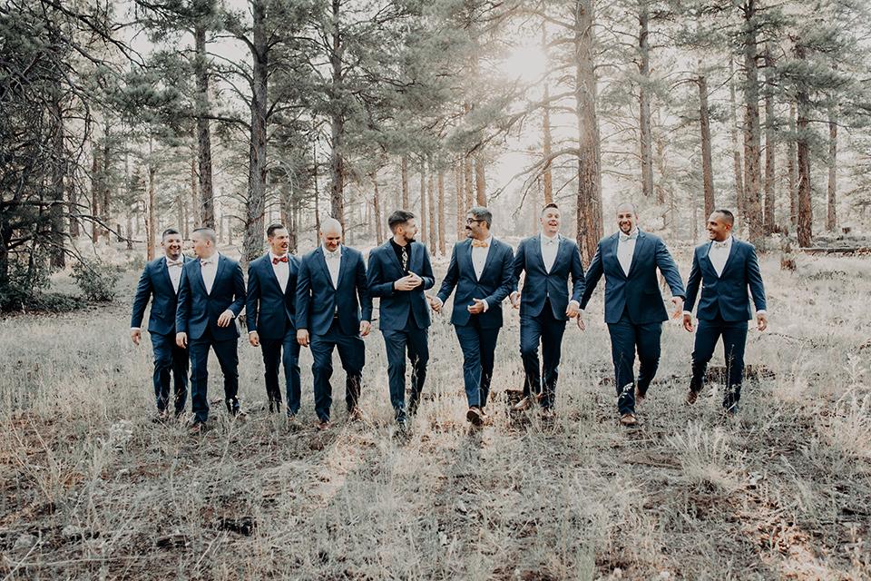 groom and groomsmen in dark blue suits with bow ties