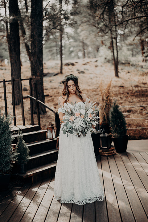 bride in a bohemian gown with an off the shoulder detail and a floral crown