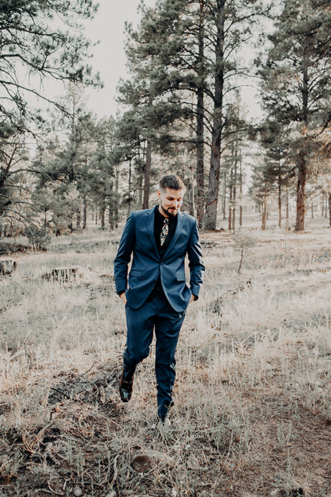 the groom in a blue suit with bow tie