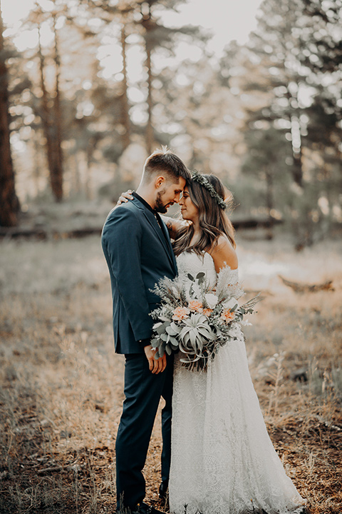 bride in a bohemian gown with an off the shoulder detail and a floral crown and the groom in a blue suit with bow tie