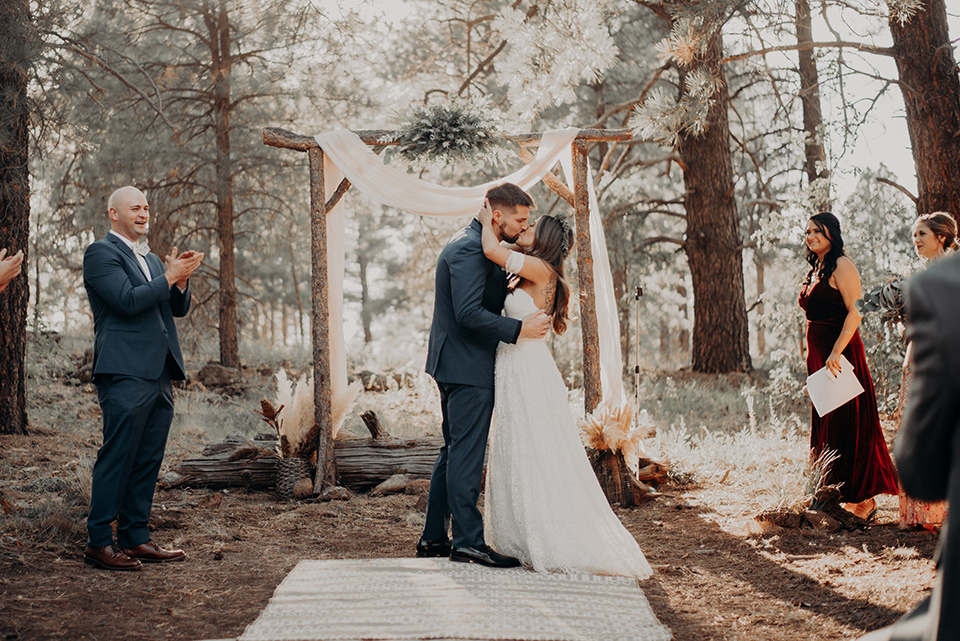 groom and groomsmen in dark blue suits with bow ties, bridesmaids in soft pastel colors in different patterns and designs, the bride in a flowing white gown with an off the shoulder detail