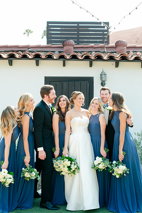 bride in a ballgown with a sweetheart neckline and bridesmaids in deep teal gowns and the bridesman in a black tux with blue bow tie