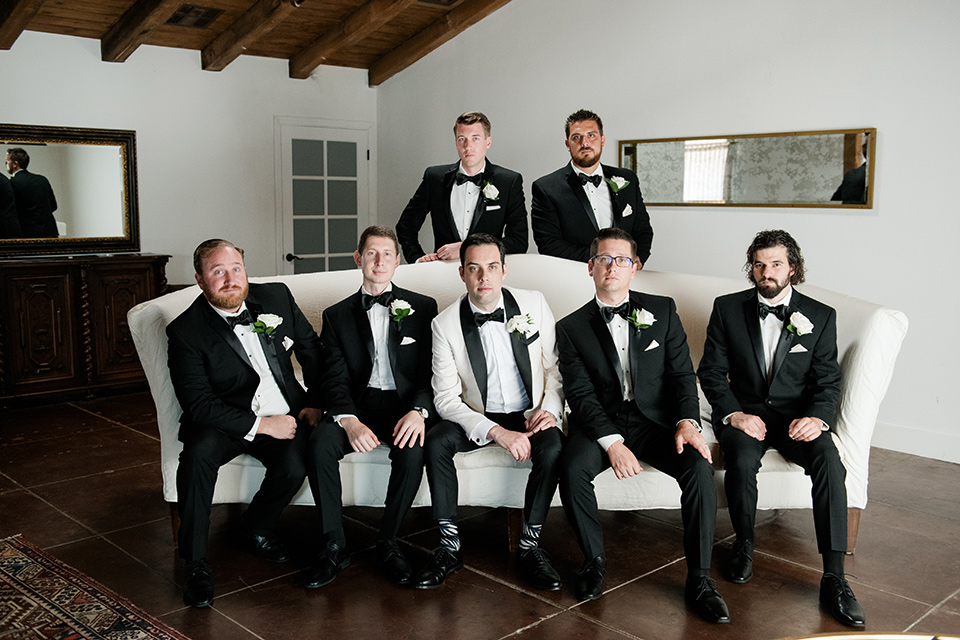 bride in a ballgown with a sweetheart neckline and the groom in a black tuxedo, the bridesmaids wore deep teal blue gowns and the groomsmen in a black tuxedo with blue bow ties