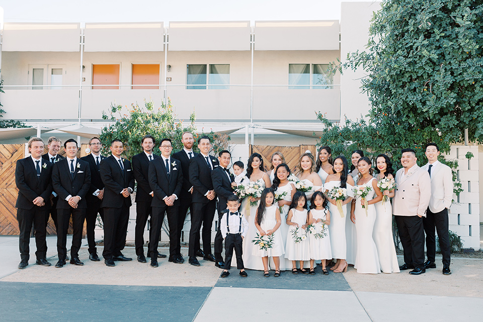 bride in a white modern gown with a low cut neckline and pockets and the groom in a black tuxedo and bow tie, the bridesmaids in neutral colored gowns and groomsmen in black tuxedos