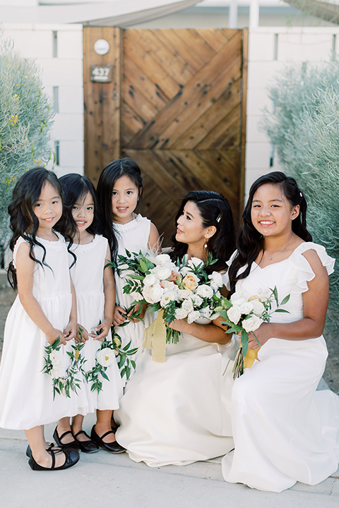 bride in a white modern ballgown with pockets and a low cut neckline and bridesmaids in neutral gowns