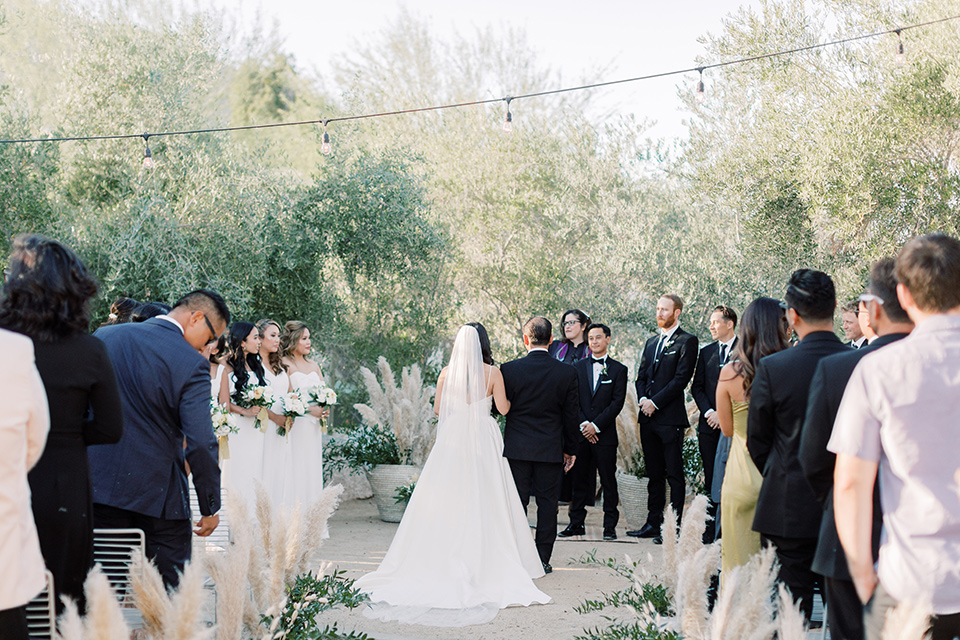 bride in a white modern gown with a low cut neckline and pockets and the groom in a black tuxedo and bow tie, the bridesmaids in neutral colored gowns and groomsmen in black tuxedos at the ceremony