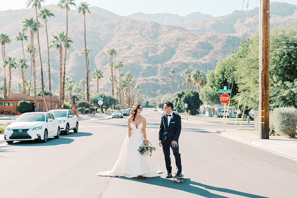 bride in a white modern gown with a low cut neckline and pockets and the groom in a black tuxedo and bow tie, the bridesmaids in neutral colored gowns and groomsmen in black tuxedos at the reception
