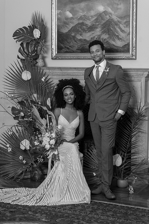 bride in a white lace formfitting gown with a V-neckline, and the groom in a café brown suit a dusty teal long tie