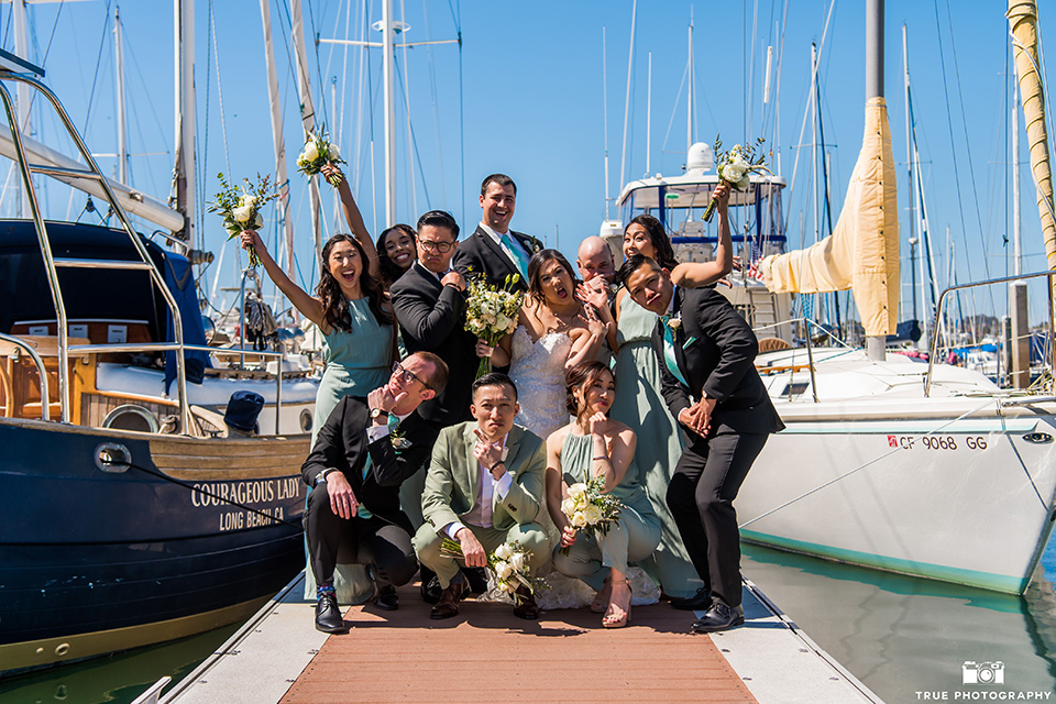 bride in a white lace form fitting gown with a strapless sweetheart neckline, the groom in a black tuxedo with a black bow tie, the groomsmen in black tuxedos with teal bow ties, the the bridesmaids in mint blue gowns and the bridesman in a mint suit to match the girls' gown