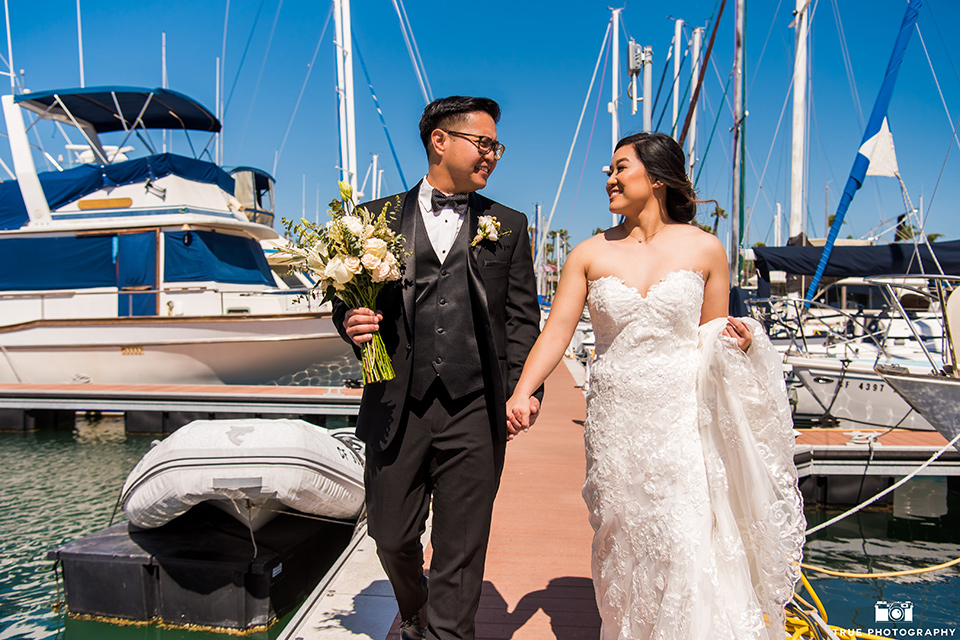 bride in a white lace form fitting gown with a strapless sweetheart neckline, the groom in a black tuxedo with a black bow tie, by the boats in the marina