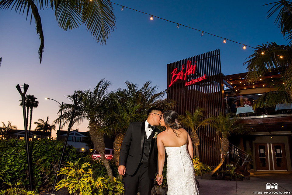 bride in a white lace form fitting gown with a strapless sweetheart neckline, the groom in a black tuxedo with a black bow tie, outside venue