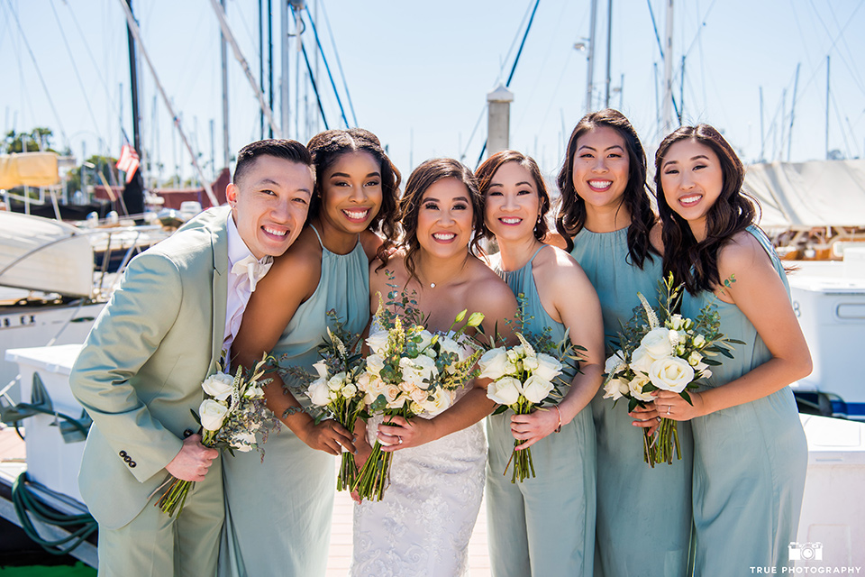 bride in a white lace form fitting gown with a strapless sweetheart neckline, the the bridesmaids in mint blue gowns and the bridesman in a mint suit to match the girls' gown