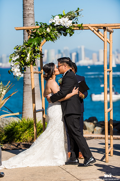bride in a white lace form fitting gown with a strapless sweetheart neckline, the groom in a black tuxedo with a black bow tie