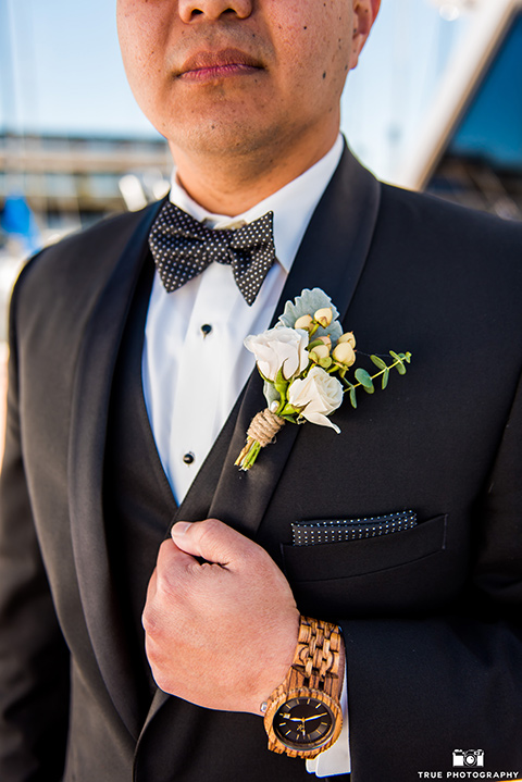 the groom in a black tuxedo with a black bow tie