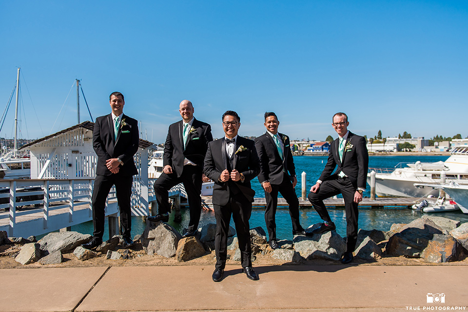 the groom in a black tuxedo with a black bow tie, the groomsmen in black tuxedos with teal bow ties