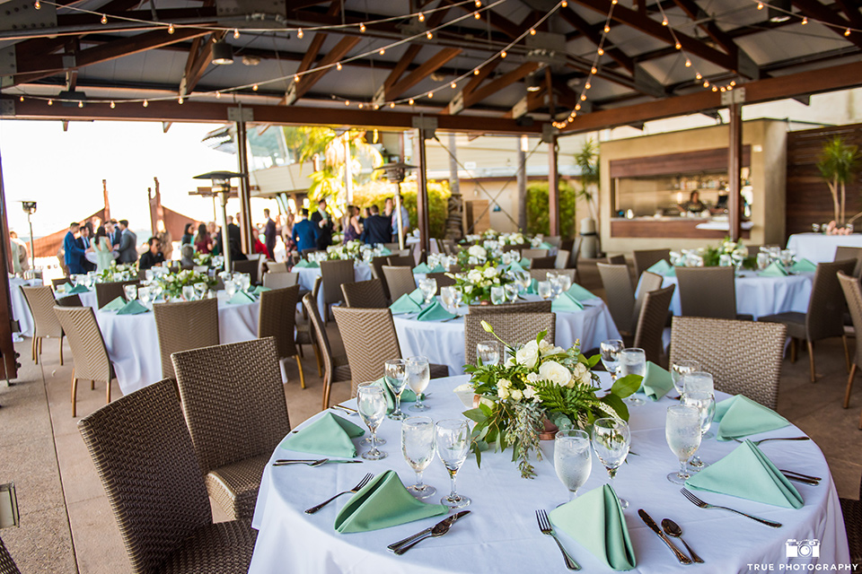 white table linens with mint green and gold details