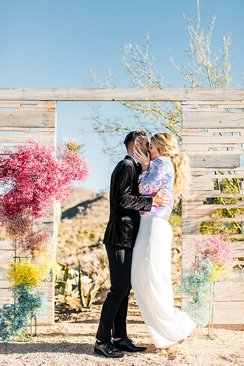 bride was in a white strapless jumpsuit with a colorful jacket and hair in a ponytail and the groom in a black paisley tuxedo with a peak lapel and black bow tie