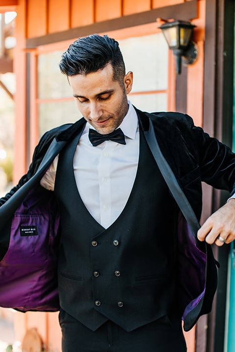 the groom in a black velvet tuxedo with a peak lapel and black bow tie
