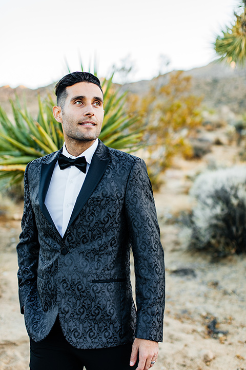 the groom in a black paisley tuxedo with a peak lapel and black bow tie