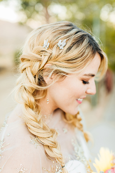 bride was in a white strapless jumpsuit with a colorful jacket and hair in a ponytail