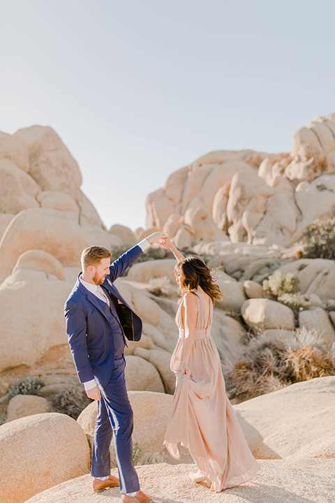 bride in a taupe colored maxi dress with straps and her hair down the groom in a cobalt blue suit with a neutral colored tie, dancing