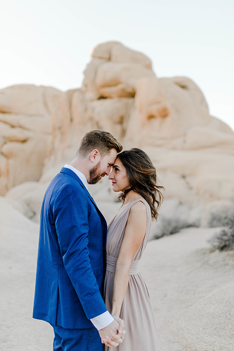 bride in a taupe colored maxi dress with straps and her hair down the groom in a cobalt blue suit with a neutral colored tie, looking at each other and touching heads
