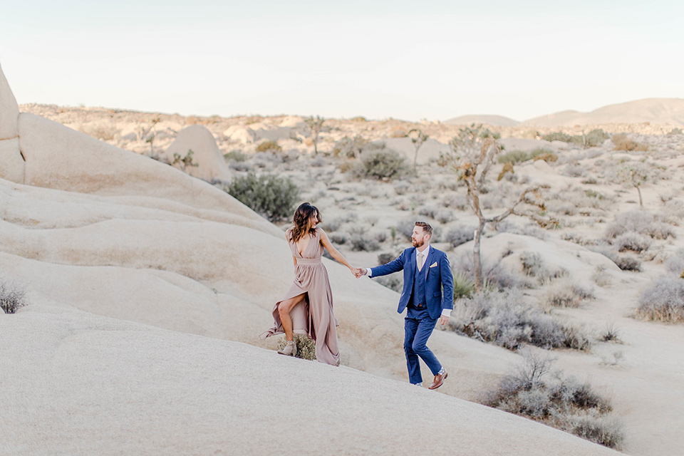 bride in a taupe gown with ankle boots and straps, the groom in a cobalt blue suit with a neutral colored tie walking up a sand dune