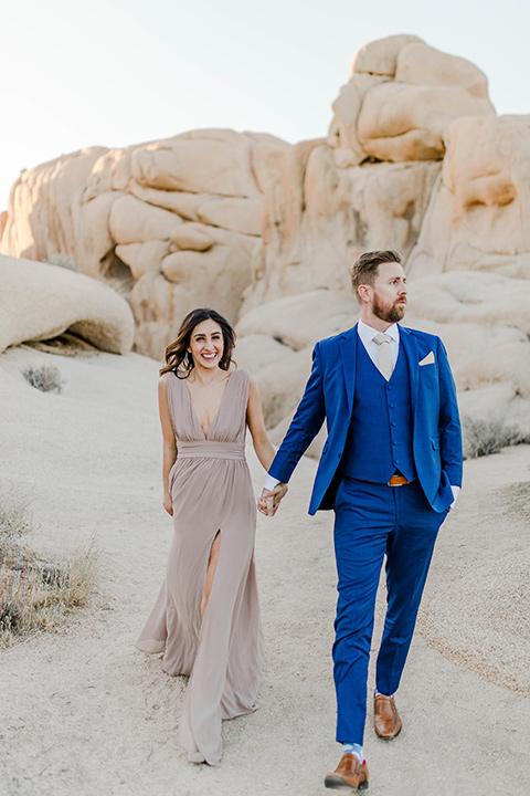 bride in a taupe maxi gown with straps and her hair down, the groom in a cobalt blue suit with a neutral long tie, walking on dune