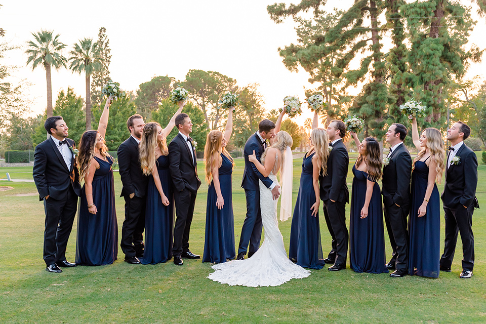 bride in a formfitting gown with thin straps and lace details, the groom in a navy tuxedo, the bridesmaids in black off-the-shoulder gowns, and the groomsmen in black tuxedos