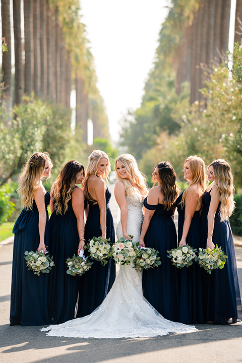 bride in a formfitting gown with thin straps and lace details, bridesmaids in black off the shoulder gowns