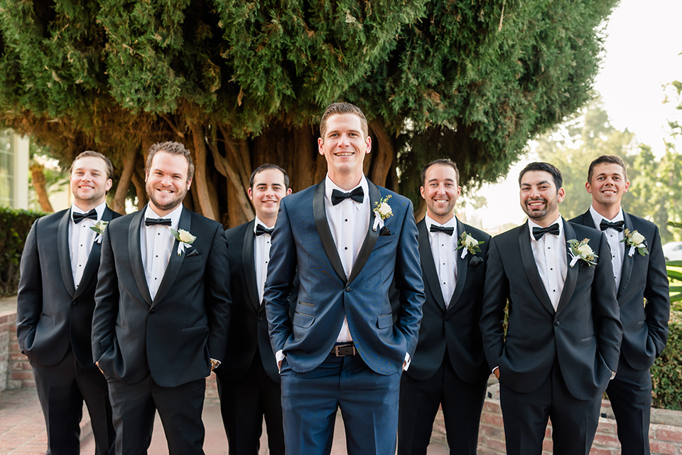 the groom in a navy tuxedo and the groomsmen in black tuxedos
