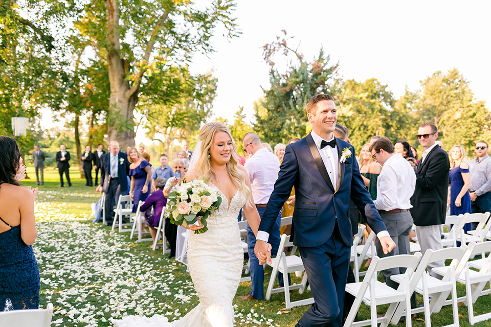 bride in a formfitting gown with thin straps and lace details, the groom in a navy tuxedo