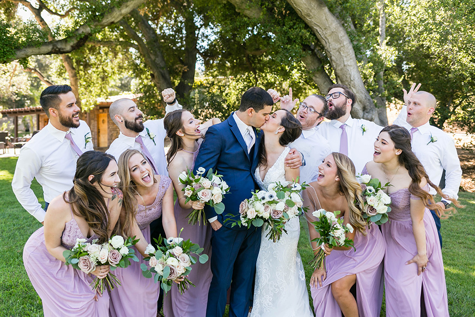 bride in a lace form-fitting gown with straps, the groom in a dark blue suit with a white long tie, the bridesmaids in lavender gowns, the groomsmen in blue pants and lavender long ties