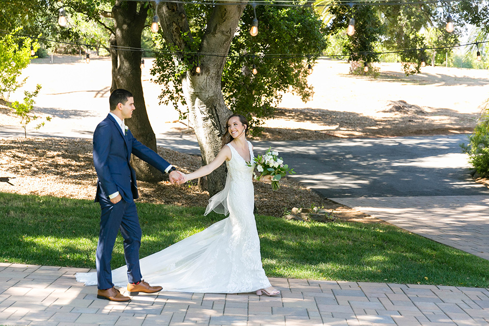 bride in a lace form-fitting gown with straps, the groom in a dark blue suit with a white long tie