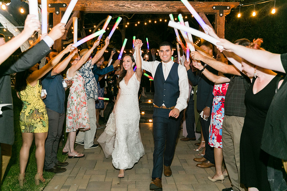bride in a lace form-fitting gown with straps, the groom in a dark blue suit with a white long tie walking away from wedding