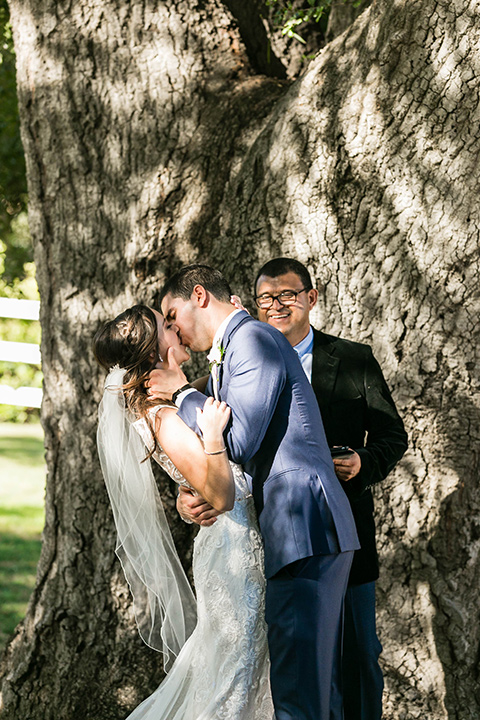 bride in a lace form-fitting gown with straps, the groom in a dark blue suit with a white long tie first kiss