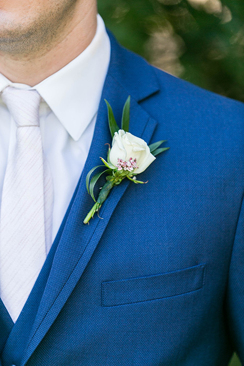 groom in a dark blue suit with a white long tie